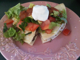 Black bean and cheese quesadilla, topped with lettuce, tomato, cilantro and sour cream.
